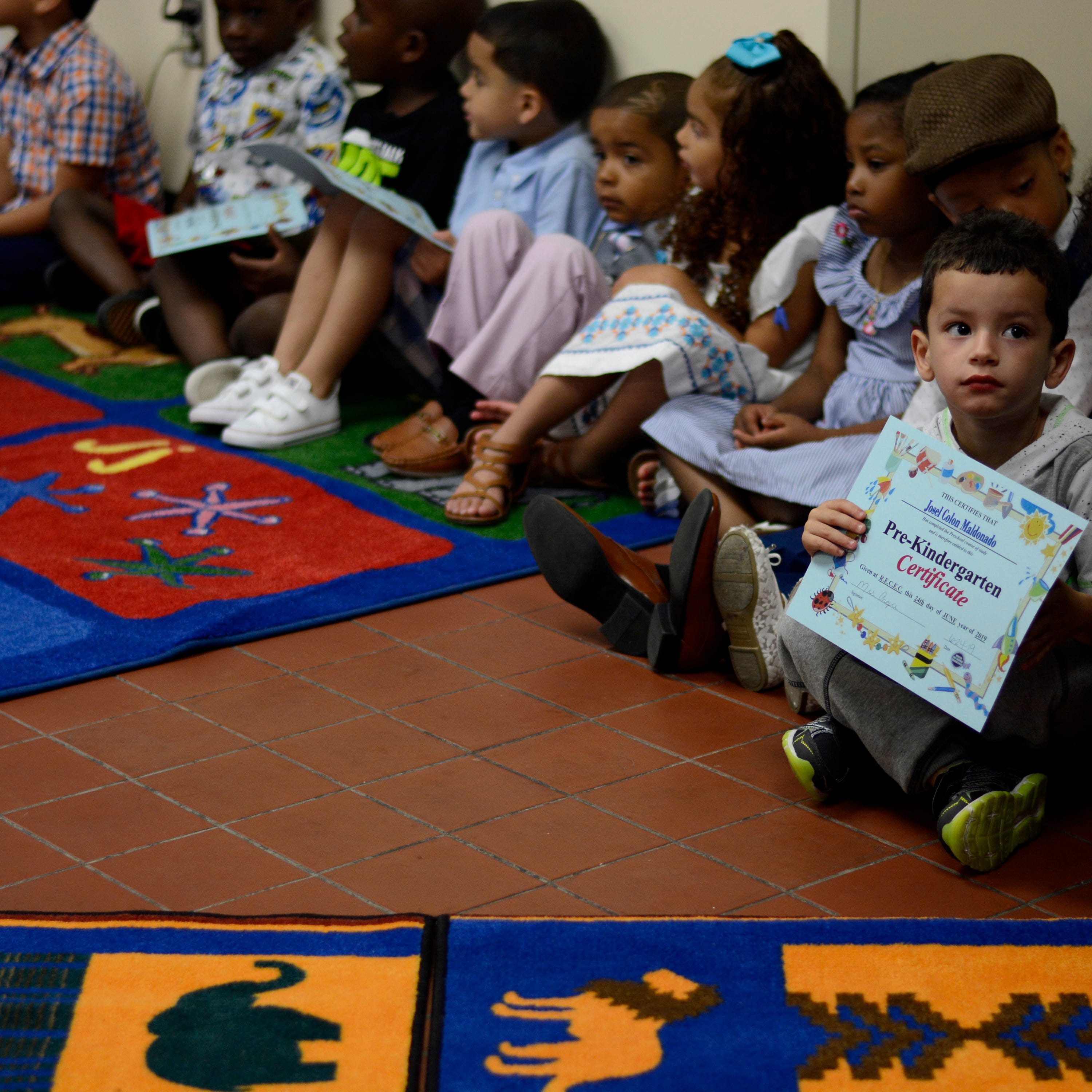 Josel Colon Maldonado sits with his pre-kindergarten class after the group performed a song for their families.